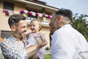 Happy gay couple with their child in the garden - MRAF00232