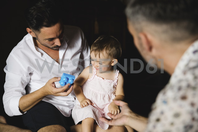 Gay couple playing with their little daughter at home - MRAF00238