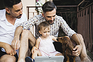 Gay couple with daughter and dog on balcony using digital tablet - MRAF00241