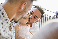 Affectionate gay couple with daughter on balcony - MRAF00247