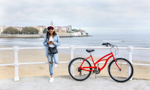 Spain, Gijon, young woman with cell phone and headphones at waterfront promenade - MGOF03571