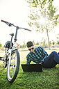 Young man with bicycle using laptop in a park - RAEF01905