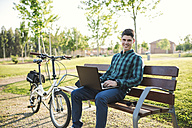 Young man with bicycle using laptop on park bench - RAEF01908