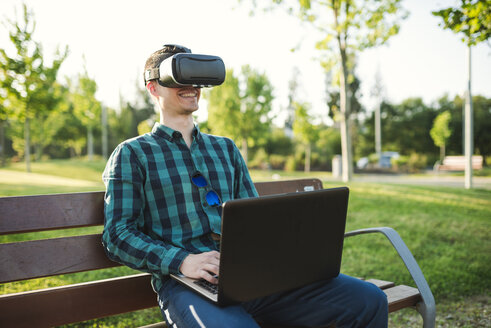 Young man working with VR glasses and laptop on park bench - RAEF01914
