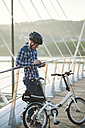 Young man with folding bicycle on a bridge looking at tablet - RAEF01920