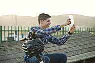 Smiling young man with bicycle taking a selfie with a tablet - RAEF01923