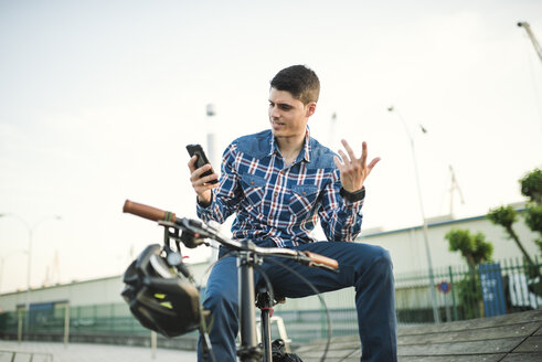 Young man with bicycle looking at smartphone and gesturing - RAEF01926