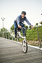Young man doing tricks with a folding bike - RAEF01932
