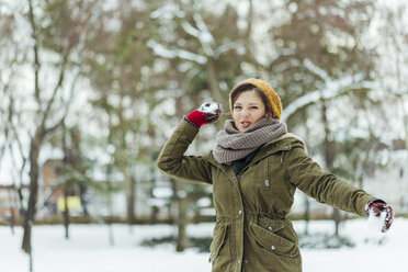 Portrait of woman throwing snowball - ZEDF00803