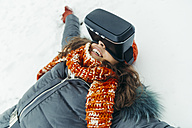 Woman lying in the snow wearing Virtual Reality Glasses - ZEDF00812