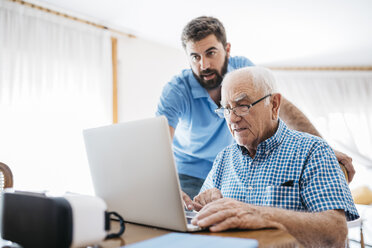 Adult grandson teaching his grandfather to use laptop - JRFF01415