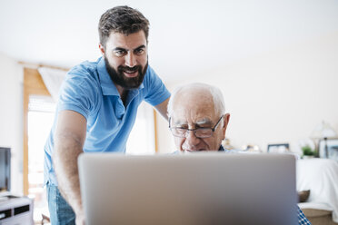 Adult grandson teaching his grandfather to use laptop - JRFF01418
