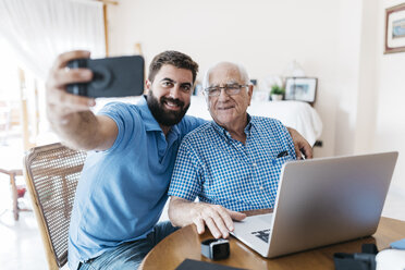 Portrait of adult grandson and his grandfather taking selfie with smartphone at home - JRFF01421