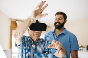 Senior man using Virtual Reality Glasses at home while his adult grandson watching him - JRFF01424