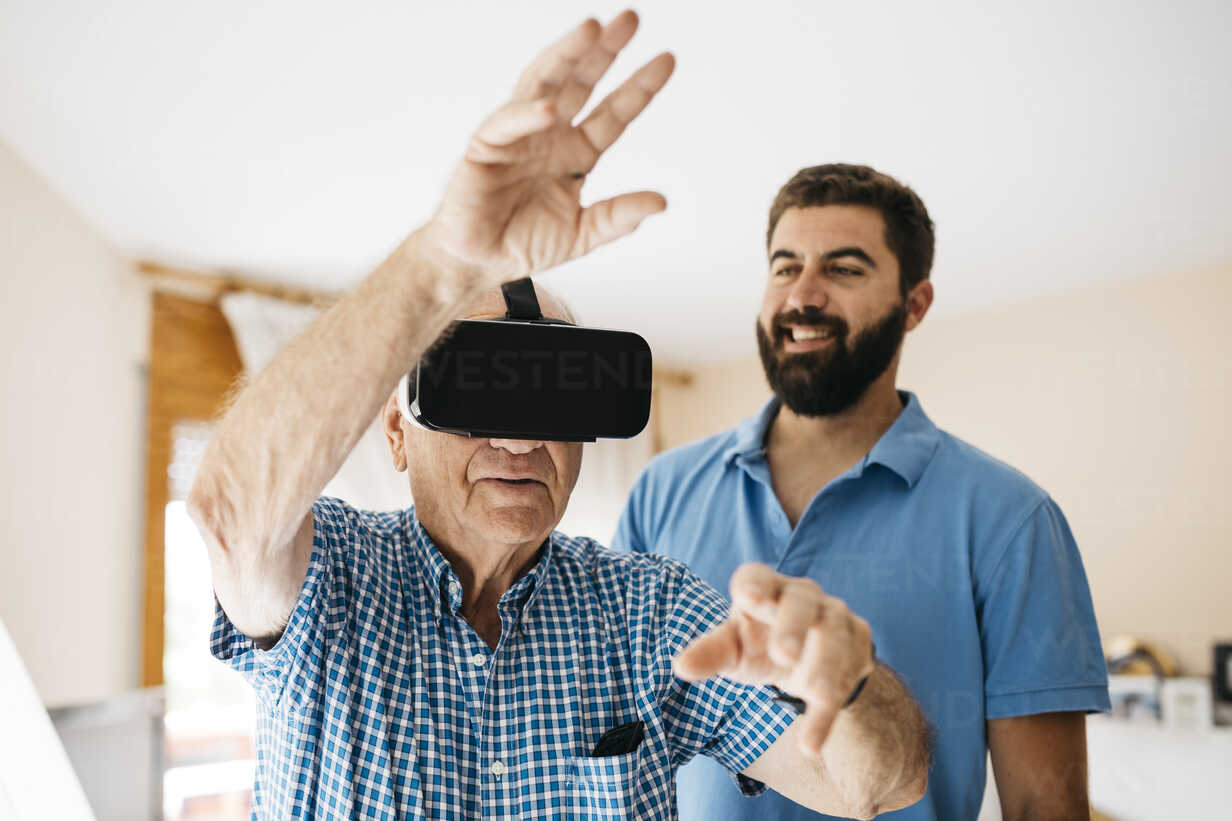 Senior man using Virtual Reality Glasses at home while his adult grandson watching him - JRFF01424 - Josep Rovirosa/Westend61