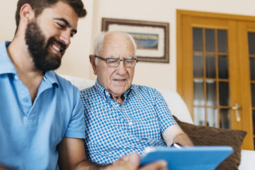 Adult grandson teaching his grandfather to use tablet - JRFF01427