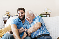 Adult grandson and his grandfather sitting on the couch at home tickling each other - JRFF01430