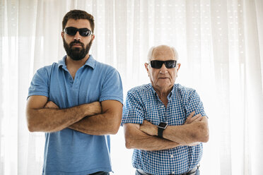 Portrait of adult grandson and his grandfather wearing sunglasses at home - JRFF01436