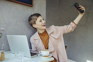 Woman taking a selfie with her laptop in a cafe - MFF03832