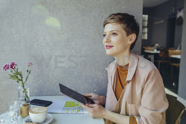 Woman with a tablet in a cafe looking sideways - MFF03835