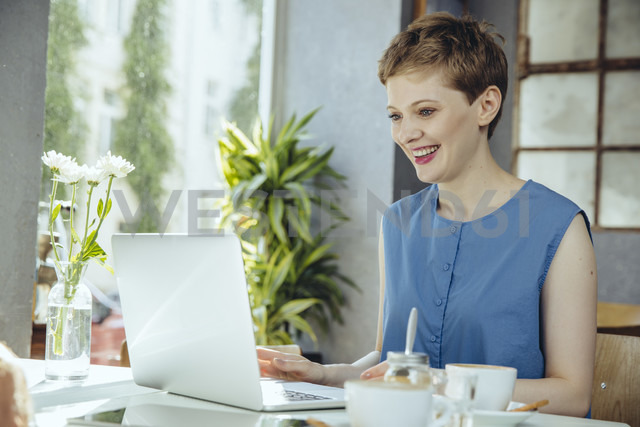 Smiling woman working in cafe with her laptop - MFF03850