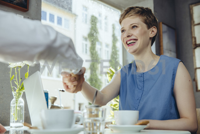 Businessman and businesswoman shaking hands in a cafe - MFF03853 - Mareen Fischinger/Westend61