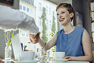 Businessman and businesswoman shaking hands in a cafe - MFF03853