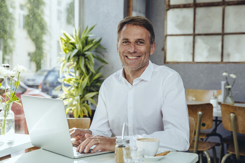 Portrait of smiling businessman working in cafe with laptop - MFF03856