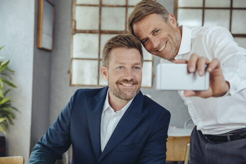 Two businessmen taking a selfie in a cafe - MFF03862