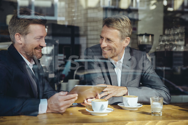 Two smiling businessmen with tablet in a cafe - MFF03865