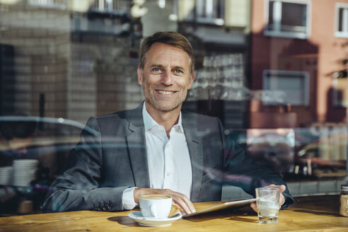 Portrait of smiling businessman with tablet in cafe - MFF03868