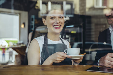 Smiling waitress serving coffee to customer in cafe - MFF03871