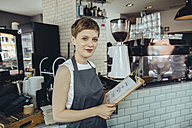 Portrait of waitress holding menu in a cafe - MFF03874