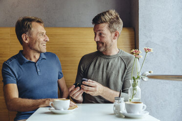 Gay man offering wedding ring to partner in cafe - MFF03895