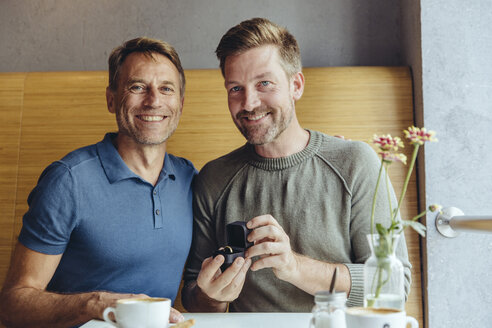 Portrait of gay couple with wedding ring in cafe - MFF03898