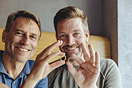Happy gay couple holding up their wedding rings - MFF03901