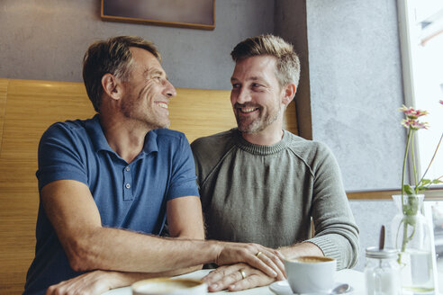 Gay couple putting their hands together with wedding rings in cafe - MFF03904