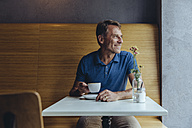 Smiling mature man sitting in cafe - MFF03907