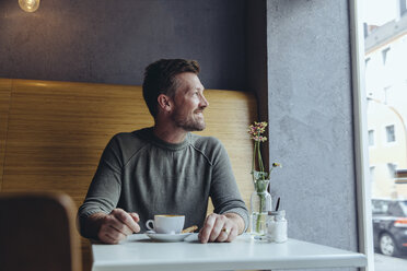 Smiling mature man sitting in cafe looking out of window - MFF03910