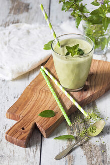 Glass of green smoothie with coconut milk, banana, matcha powder garnished with mint leaves - YFF00677