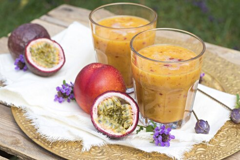 Two glasses of fruit smoothie with passion fruit, nectarine, pomegranate juice and rice milk - YFF00680