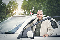Portrait of smiling mature businessman entering his car - JUNF00885