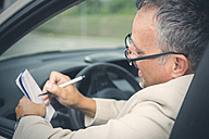 Businessman sitting in his car making notes - JUNF00888