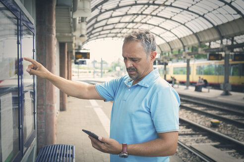 Man with smartphone standing on platform in front of timetable - JUNF00891