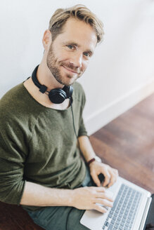 Portrait of smiling man with headphones and laptop - GIOF03165