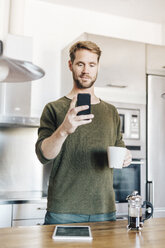 Portrait of man standing in kitchen with cup of coffee taking selfie with smartphone - GIOF03171