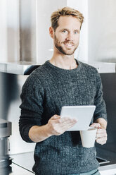 Portrait of smiling man standing in kitchen with tablet and coffee mug - GIOF03174