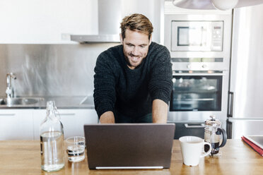 Portrait of smiling man standing in kitchen using laptop - GIOF03177