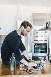 Man sitting on worktop in the kitchen using laptop - GIOF03180