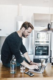 Man sitting on worktop in the kitchen using laptop - GIOF03180